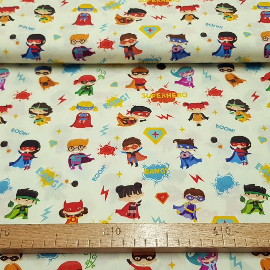 Cotton Superheroes Kids fabric - Digital print cotton fabric with drawings of girls and boys dressed as superheroes with masks, capes... on a light yellow background with drawings of rays, onomatopoeia. The fabric is 140cm wide and its composition i