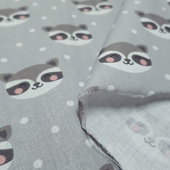 Cotton Raccoons Polka Dots fabric - Cotton fabric digital printing with drawings of raccoon heads on a gray background with white dots. The fabric is 140cm wide and its composition is 100% cotton.