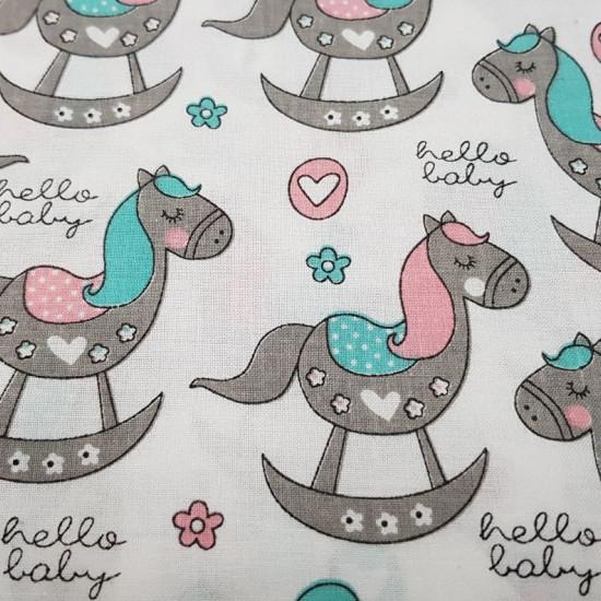 """Tela Algodón Caballitos de Madera - Tela de algodón infantil con dibujos de caballitos de madera en colores grises combinando con rosa y turquesa sobre un fondo blanco con flores, corazones y frases """"hello baby"""". La tela mide 160cm de ancho y su compos"""