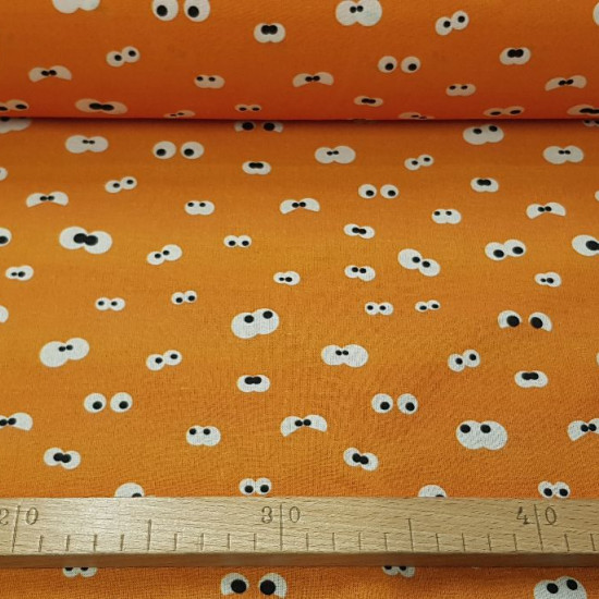 Cotton Eyes Looking Orange fabric - Cotton fabric with drawings of peeping eyes on an orange background. The fabric is 150cm wide and its composition is 100% cotton.