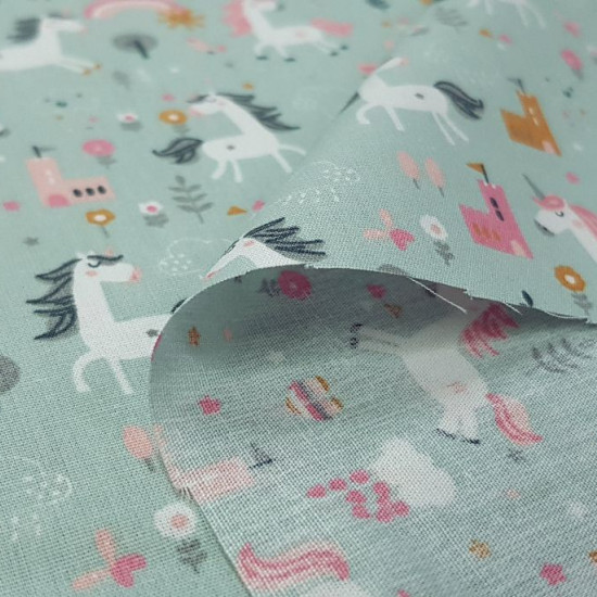 Tela Algodón Unicornios Castillos Verde - Tela de algodón infantil con dibujos de unicornios sobre un fondo de color verde con castillos, plantas, arcoiris... La tela mide 150cm de ancho y su composición 100% algodón.