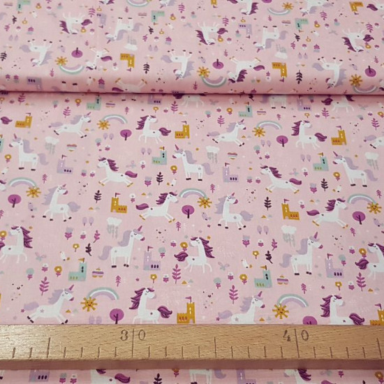 Cotton Unicorns Castles Pink fabric - Children's cotton fabric with drawings of unicorns, castles, rainbows... on a pink background. The fabric is 150cm wide and its composition is 100% cotton.