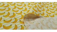 Cotton Striped Bananas fabric - Cotton fabric with drawings of bananas on a yellow striped background. The fabric is 150cm wide and its composition is 100% cotton.