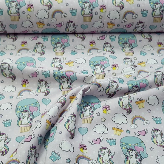 Cotton Unicorns Rainbow Hair fabric - Children's cotton fabric with drawings of unicorns with colored hair, clouds, balloons, rainbows, colored stars on a light background. The fabric is 140cm wide and its composition is 100% cotton.