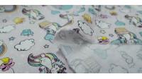 Tela Algodón Unicornios Pelo Arcoiris - Tela de algodón infantil con dibujos de unicornios con pelo de colores, nubes, globos, arcoiris,estrellas de colores sobre un fondo claro. La tela mide 140cm de ancho y su composición 100% algod&o