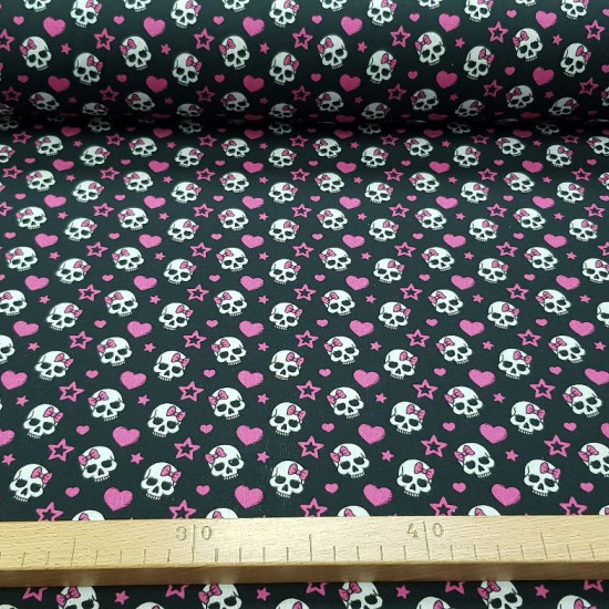 Cotton Skulls Pink Bows fabric - Cotton fabric with drawings of skulls with pink bows on a black background with pink hearts and stars. The fabric is 140cm wide and its composition is 100% cotton.