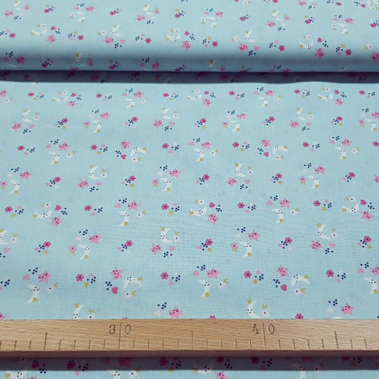 Cotton Moons and Stars Blue fabric - Children's cotton fabric with drawings of moons and stars with crowns on a light blue background with flowers and hearts. The fabric is 150cm wide and its composition is 100% cotton.