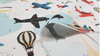 Cotton Airplanes and Stars fabric - Children's themed cotton satin fabric with colorful drawings of airplanes and helicopters on a white and blue background with stars in bright colors The fabric is 140cm wide and its composition is 100% cotton.