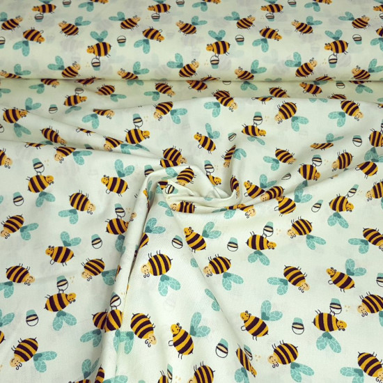 Cotton Bees Honey fabric - Cotton poplin fabric with drawings of bees with honey cubes on a light yellow background. The fabric is 150cm wide and its composition is 100% cotton.