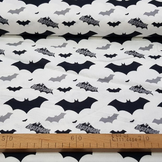 Cotton Batman Bats fabric - Cotton fabric with bat drawings and Batman logos in black and gray tones on a white background. The fabric is 140cm wide and its composition is 100% cotton.