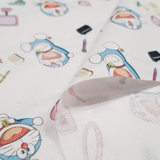 Cotton Doraemon Magic Items fabric - Children's cotton fabric with drawings of the character Doraemon and magical objects around him on a white background. The fabric is 150cm wide and its composition is 100% cotton.
