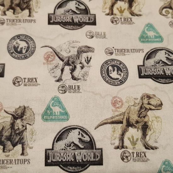 Tela Algodón Jurassic World Dinosaurios - Tela de algodón licencia con dibujos de dinosaurios y parches de la película Jurassic World sobre un fondo claro. La tela mide 150cm de ancho y su composición 100% algodón.