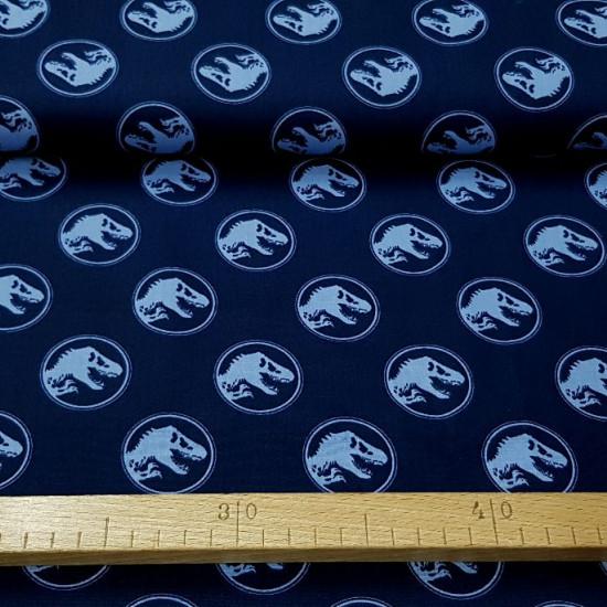 Tela Algodón Jurassic Logos Azul - Tela de algodón con dibujos de logos de Jurassic Park de color azul claro sobre un fondo de color azul oscuro. La tela mide 150cm de ancho y su composición 100% algodón.