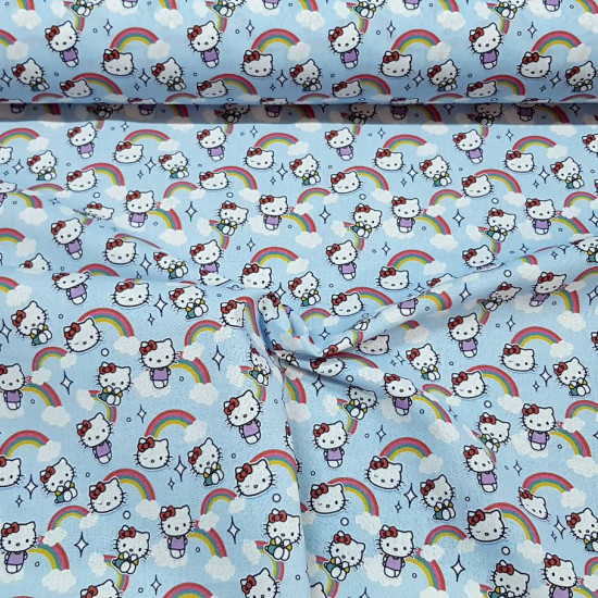 Hello Kitty Cotton Clouds Blue fabric - Licensed cotton fabric with drawings of the character Hello Kitty on a background in blue with rainbows and clouds. The fabric measures between 140-150cm wide and its composition is 100% cotton.