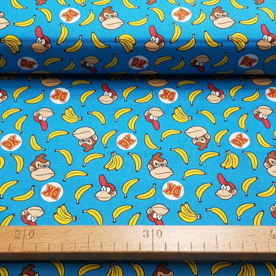 Cotton Donkey Kong Bananas fabric - Licensed cotton fabric with drawings of thecharacters from the classic video game Donkey Kong on a blue background with bananas. The fabric is 110cm wide and its composition is 100% cotton.