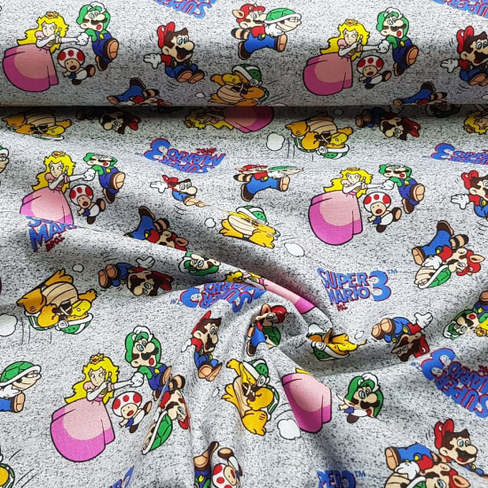 Cotton Super Mario Bros 3 fabric - Licensed cotton fabric with drawings of the characters from the video game Super Mario Bros 3, on a gray background. Mario, Luigi, Peach, Toad characters appear... The fabric is 110cm wide and its composition is 100%