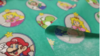 Cotton Super Mario Round Frames fabric - Licensed cotton fabric with drawings of the characters from the video game Super Mario inside round frames on a green background. The fabric is 110cm wide and its composition is 100% cotton.