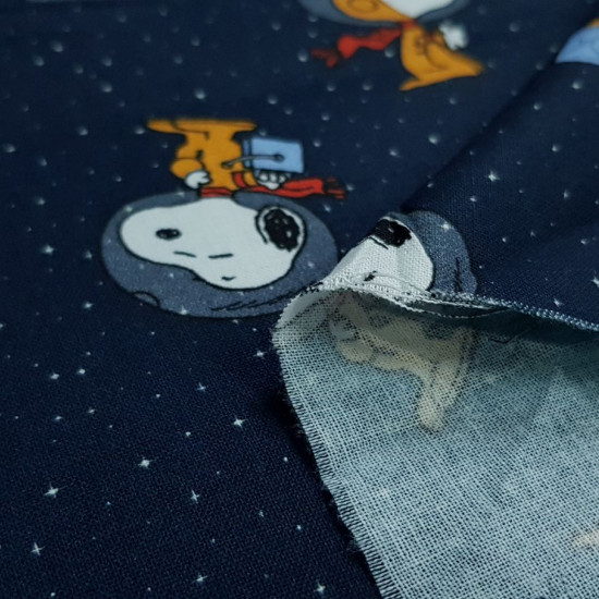 Cotton Snoopy Astronaut fabric - Licensed cotton poplin fabric with drawings of the character Snoopy in an astronaut suit on a dark blue background with little stars. The fabric is 140cm wide and its composition is 100% cotton.