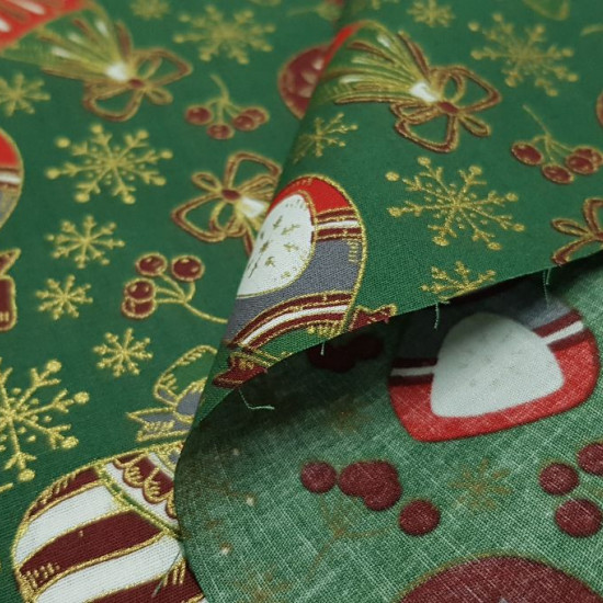 Cotton Christmas Ornaments and Green Flakes fabric - Christmas-themed cotton fabric with drawings of Christmas ornaments, golden snowflakes and several more ornaments on a green background. The fabric is 150cm wide and its composition 100% cotton
