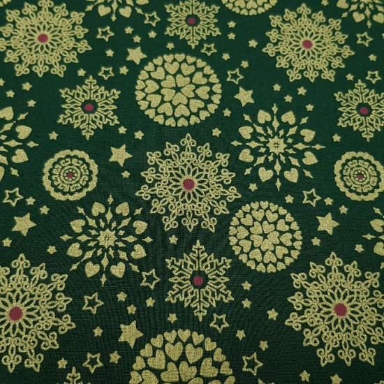 Cotton Christmas Flakes Hearts Green Background fabric - Christmas cotton fabric with bright gold patterns with snowflakes, stars and circles formed by hearts on a green background. The fabric is 140cm wide and its composition 100% cotton.