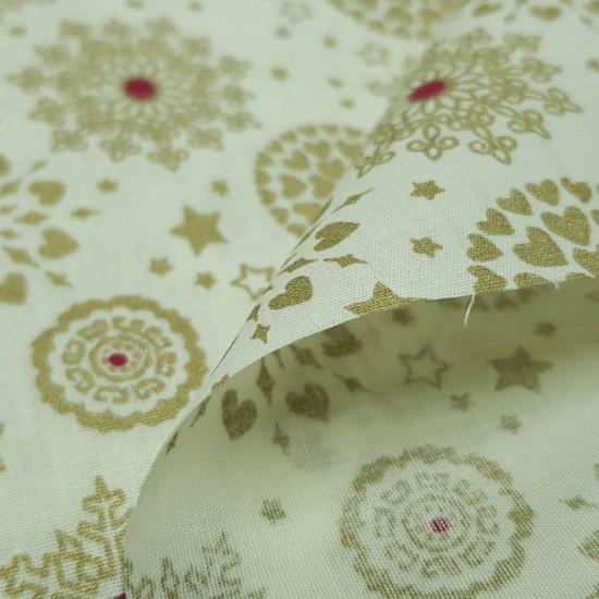 Tela Algodón Navidad Copos Corazones - Tela de algodón con dibujos navideños de copos de nieve dorados, corazones haciendoforma de círculo y estrellas sobre un fondo blanco crudo. La tela mide 140cm de ancho y su composición 100% algodón.