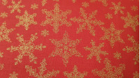 Cotton Christmas Golden Stars Red fabric - Cotton fabric with drawings of stars or golden flakes on a red background. The fabric is 150cm wide and its composition is 100% cotton.