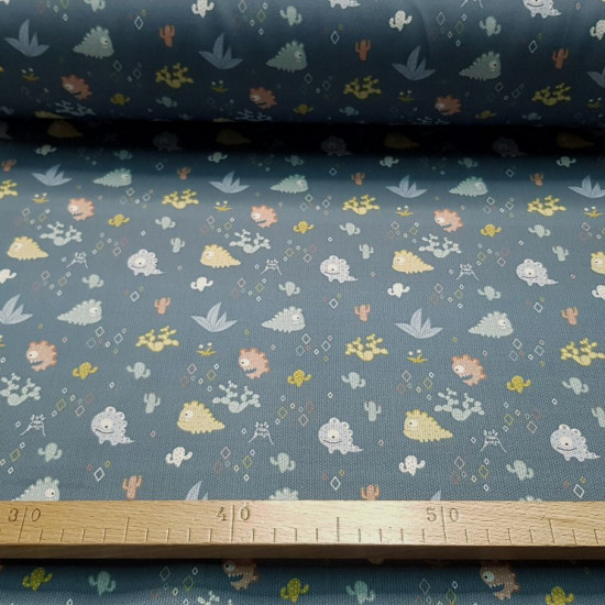 Pique Funny Monsters Gray fabric - Pique fabric for children with funny drawings of monsters on a dark gray background with cactus and volcanoes vegetation motifs. The fabric is 150cm wide and its composition is 100% cotton.