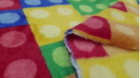 Coral Fleece Building Blocks Colors fabric - Coral fleece fabric with pictures of colored building blocks, similar of Lego blocks and others. The fabric is 150cm wide and its composition is 100% polyester.