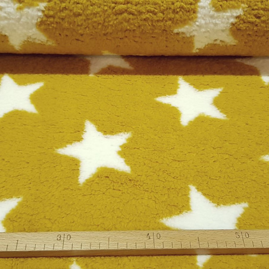 Sherpa Fleece Stars fabric - Sherpa fleece fabric with drawings of white stars on an ocher background. Sherpa fabric has a very soft touch and reminds us of a sheepskin. The fabric is 150cm wide and its composition is 100% polyester.