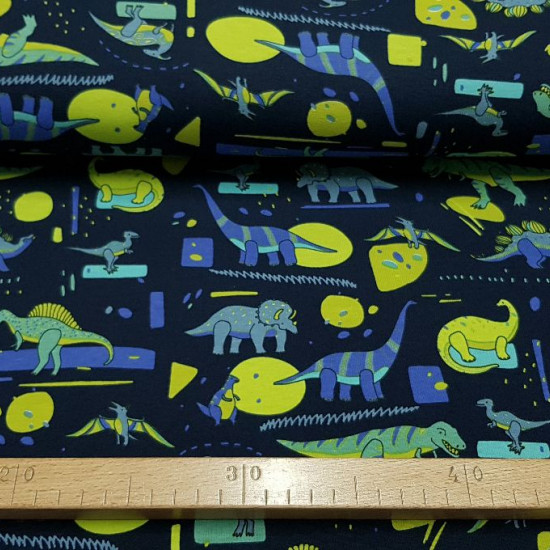 Knitted Cotton Dinosaurs Abstract Blue fabric - Cotton jersey fabric with dinosaur drawings in green and blue colors on a dark blue background with abstract shapes. The fabric measures 150cm wide and its composition 95% cotton - 5% Elastane
