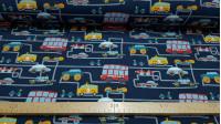 Tela Punto Algodón Tráfico Ciudad Azul - Tela de punto tipo camiseta con dibujos de coches, autobuses, coches de policia, bomberos…sobre lineas grises simulando el tráfico de una ciudad en un fondo azul oscuro. La tela mide 150cm de ancho y su composició