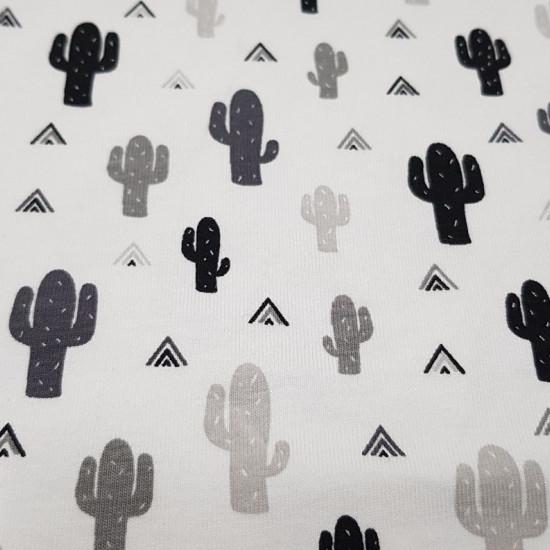 Tela Punto Algodón Cactus Tipi - Tela de punto algodón con dibujos de cactus y triángulos en forma de tiendas tipi en colores negroy grises sobre un fondo blanco. La tela mide 150cm de ancho y su composición 95% algodón –5% elastano