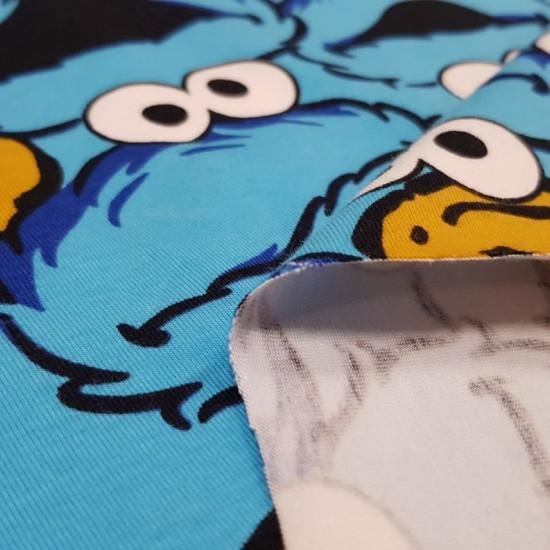 Tela Punto Algodón Monstruo Galletas Triki - Tela de punto algodón con dibujos divertidos del personaje Triki (El monstruo de las galletas) de la famosa serie El Barrio Sésamo. La tela mide 155cm y su composición 92% algodón –8% elastano