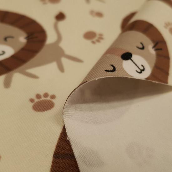 Tela Punto Algodón Orgánico Leones - Tela de punto algodón orgánico (GOTS) con dibujos de leones y huellas sobre un fondo claro. La tela mide 160cm de ancho y su composición 95% algodón –5% elastano