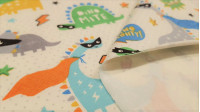 Organic Cotton Jersey Super Dinosaurs fabric - Organic Cotton Jersey Fabric (GOTS) with funny dinosaur drawings with superhero capes, masks and stars, lightning and dots background on off-white background. The fabric is 160cm wide and its composition is 9