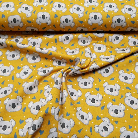 Digital Jersey Ocher Koalas fabric - Digital cotton jerseyfabric with drawings of koala faces on an ocher background with gray shapes and white dots. The fabric is 150cm wide and its composition is 94% cotton - 6% elastane.