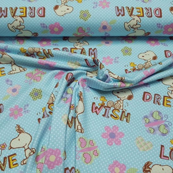"Cotton Jersey GOTS Snoopy Love fabric - Licensed organic cotton jersey fabric where the character Snoopy and the bird Emilio (Woodstock) appear on a background with white polka dots, flowers, butterflies and colored phrases like ""Dream"", ""Wish"" and ""Love"""