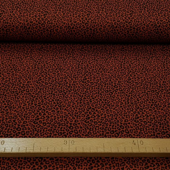 Cotton Jersey Animal Print Terracotta fabric - Cotton jerseyfabric with an animal print pattern in black on a dark terracotta background. The fabric is 150cm wide and its composition 95% cotton - 5% elastane