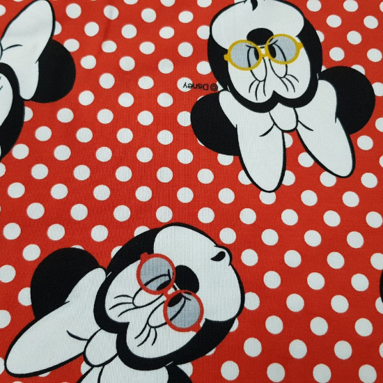 Cotton Jersey Minnie Glasses fabric - Disney licensedcotton jerseyfabric with drawings of Minnie with glasses of various colors on a red background with white polka dots. The fabric is 150cm wide and its composition 95% cotton - 5% elastane