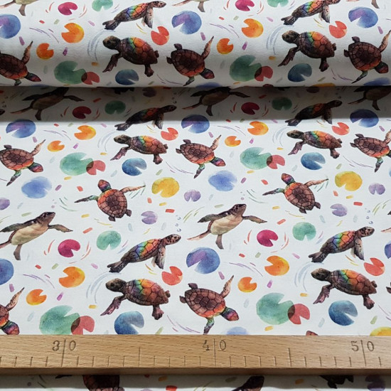 Digital Cotton Jersey Turtles fabric - Cotton jersey fabric with digital printing with drawings of turtles with colored shells and shapes of colored discs on a white background. The fabric is 150cm wide and its composition is 95% cotton - 5% elastane.