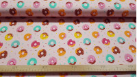 Digital Cotton Jersey Donuts Pink fabric - Cotton jerseyfabric in digital printing with drawings of colored glazed donuts on a pink background with colored confetti. The fabric is 150cm wide and its composition 94% cotton - 6% elastane