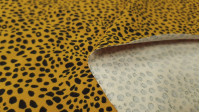 Cotton Jersey Panther Ocher fabric - Cotton jersey fabric with panther-style animal print patterns on an ocher background. The fabric is 150cm wide and its composition is 95% cotton - 5% elastane.