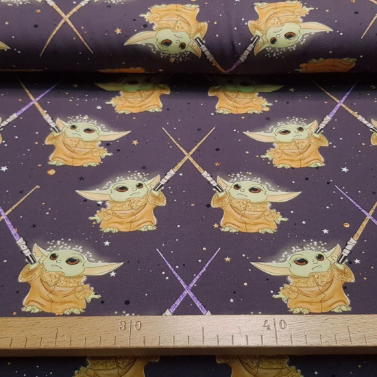 Jersey Mandalorian Baby Yoda Light Saber Dark fabric - Cotton jerseywith drawings of the character from the Star Wars The Mandalorian series, Baby Yoda with lightsabers on a dark background. The fabric is 155cm wide and its composition is 95% cotton - 5%