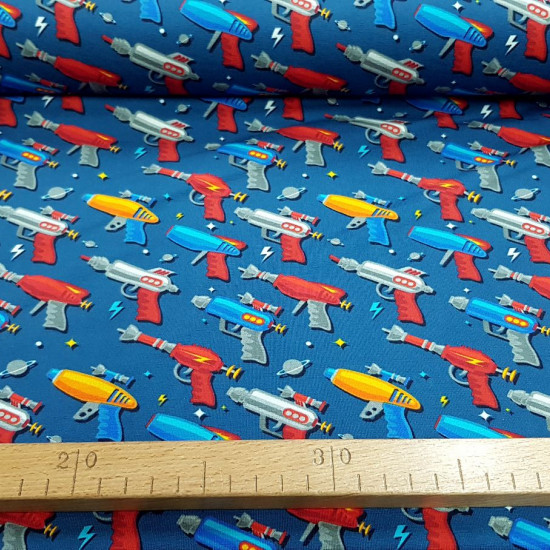 Cotton Jersey Space Toy Guns fabric - Very funny digital print cotton jersey fabric with drawings of space toy guns on a blue background. The fabric is 150cm wide and its composition is 94% cotton - 6% elastane.