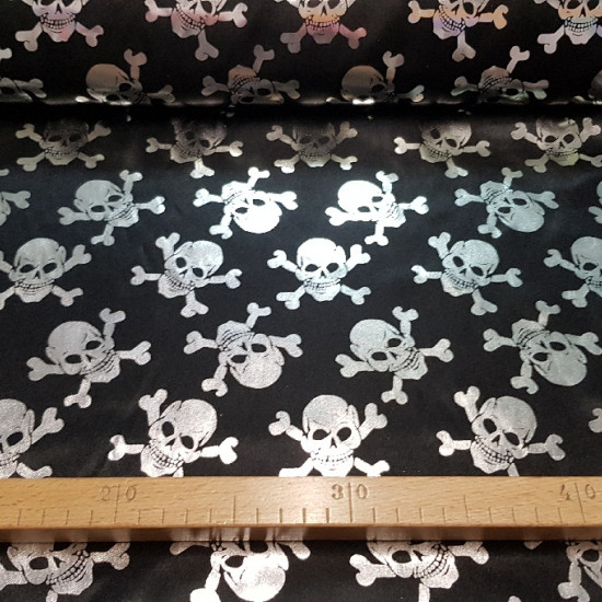 Foil Skulls fabric - Fabric with drawings of shiny silver pirate skulls on a black background. The fabric is a fine lamé/foil fabric, ideal for Halloween costumes and pirate costume accessories. The width of the fabric is 150cm and its c