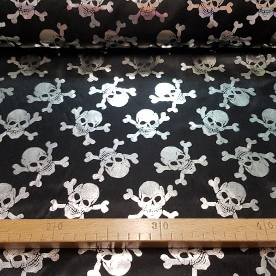 Tela Lamé Calaveras - Tela con dibujos de calaveras piratas plateadas brillantes sobre fondo negro. La tela es un tejido de lamé/foil fino, ideal para disfraces de Halloween y complementos para disfraz de pirata. El ancho de la tela es de