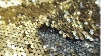 Reversible Sequins fabric - Shiny reversible sequins fabric on one side of gold and on the other side of silver, on a thin and elastic black fabric in one direction. Ideal for party dresses, shiny t-shirts, costumes... it's super pretty! The fa