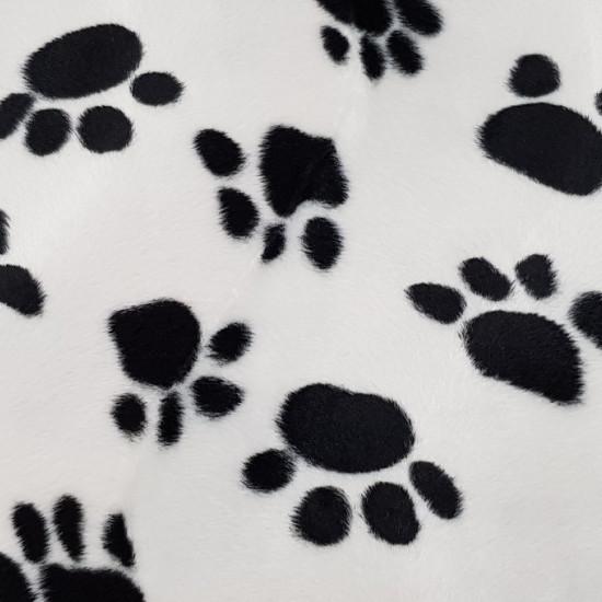 Tela Pelo Mutón Huellas - Tela de pelo corto tipo mutón estampado con dibujos de huellas negras sobre fondo blanco. Ideal para disfraces de animales y también para decoración. La tela mide 150cm de ancho y su composición 100% Poliester.