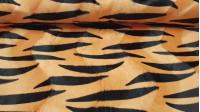 Tela Pelo Mutón Tigre - Tela de pelo corto suave tipo mutón, con dibujo estampado de rayas negras sobre un fondo naranja, imitando la piel de un tigre. La tela mide 150cm de ancho y su composición 100% poliester.