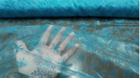 Organza Turquoise Ice Flakes fabric - Semi-transparent organza fabric with glitter and turquoise fall with bright ice flakes. Ideal for ice princess costume (Frozen), decorations and much more. The fabric is 150cm wide and its composition 100% polyester.